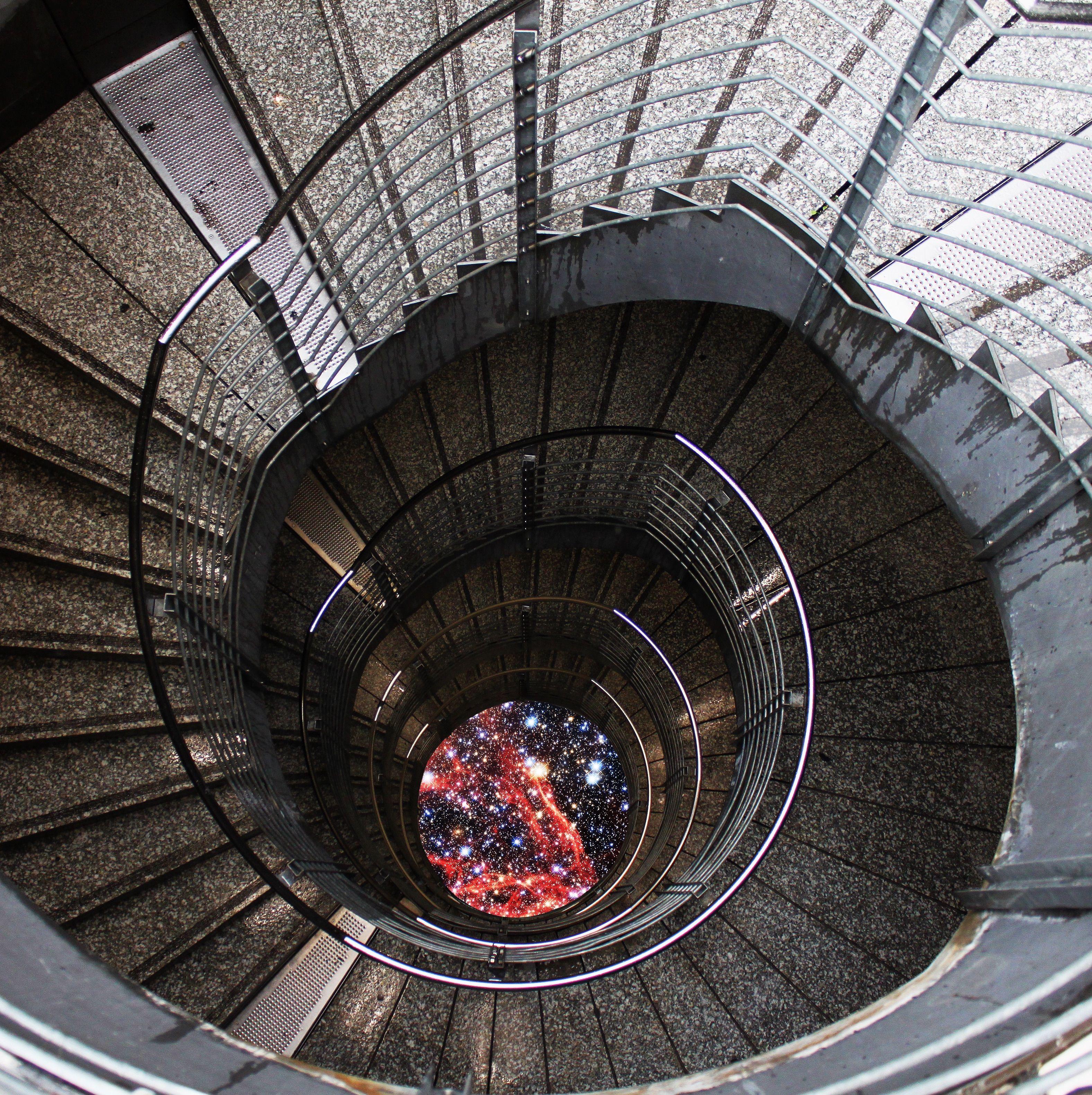 Aus der Vogelperspektive sieht eine:r eine Wendeltreppe, die nach unten führt. Anstelle des Bodens sieht eine:r ein Bild vom Universum in der Mitte der Treppe.