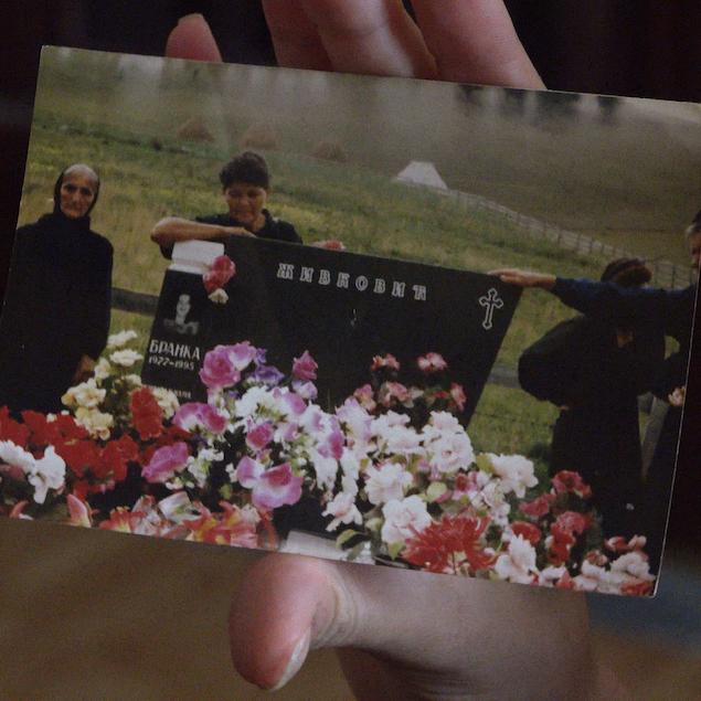 Eine Hand hält ein Foto, auf dem zwei Frauen hinter einem schwarzen Grabsein mit kyrillischer Schrift stehen. Vor dem Grabstein sind viele bunte Blumen.