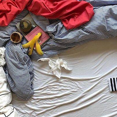 Ein Bett aus einer Vogelperspektive. Darauf blau gestreifte zerknautschte Bettwäsche, ein Kaffeebecher, eine Bananenschale und ein rotes Tuch.