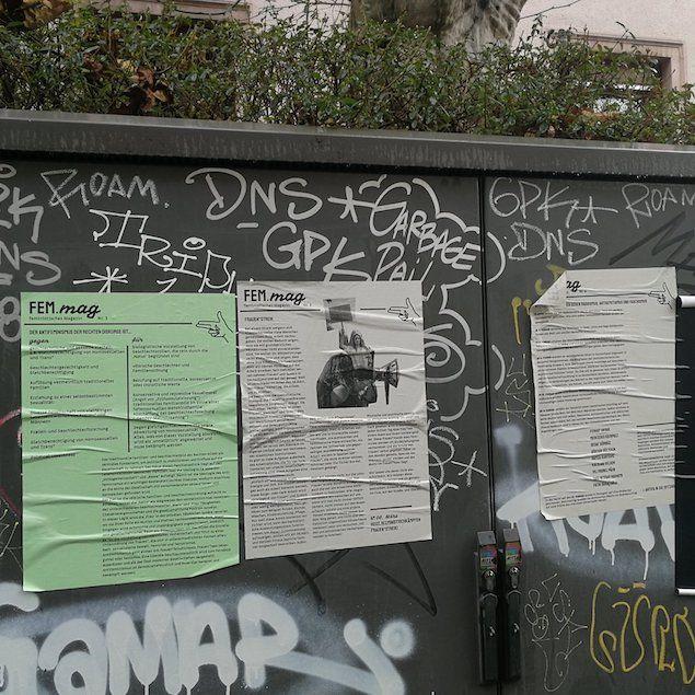 Auf einem Stromverteiler-Kasten mit Graffiti kleben drei Wandzeitungen des Fem.Mag.