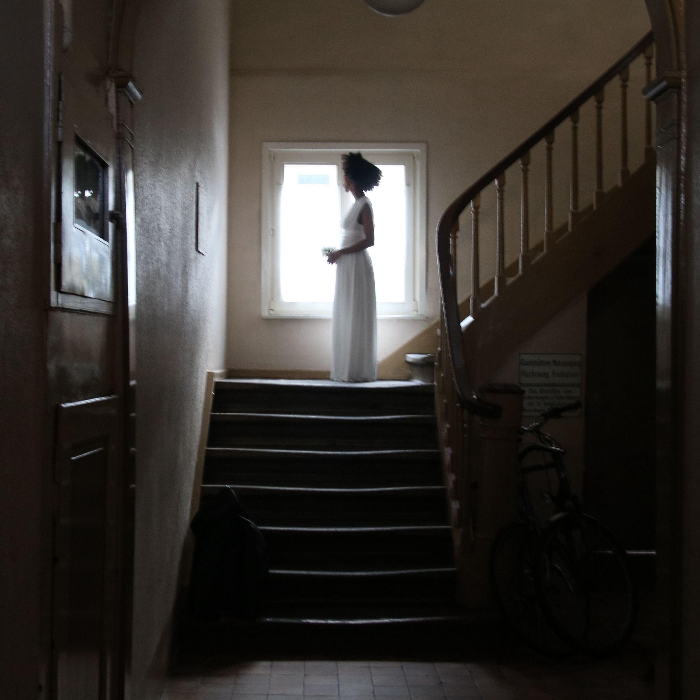Eine Person steht weit hinten im Bild in einem langen weißen Kleid auf einem Treppenabsatz vor einem Fenster im Gegenlicht. Eine:r sieht sie von der Seite, ihre Arme sind gebeugt.