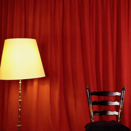 Vor einem roten Vorhang steht ein Stuhl. Links daneben ist eine Stehlampe mit gelbem Lampenschirm zu sehen.