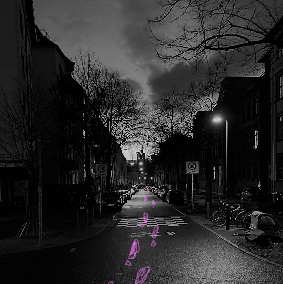 Straßenzug in schwarz/weiß, es zeichnen sich Bäume neben der in der Mitte verlaufenden Straße ab. Auf der Straße sind Fußspuren in pink auf das Bild aufgemalt.