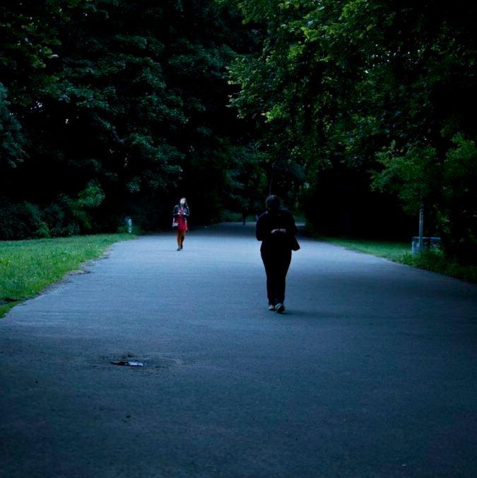 Zwei Personen laufen in der Dämmerung unter Bäumen auf einem Weg.