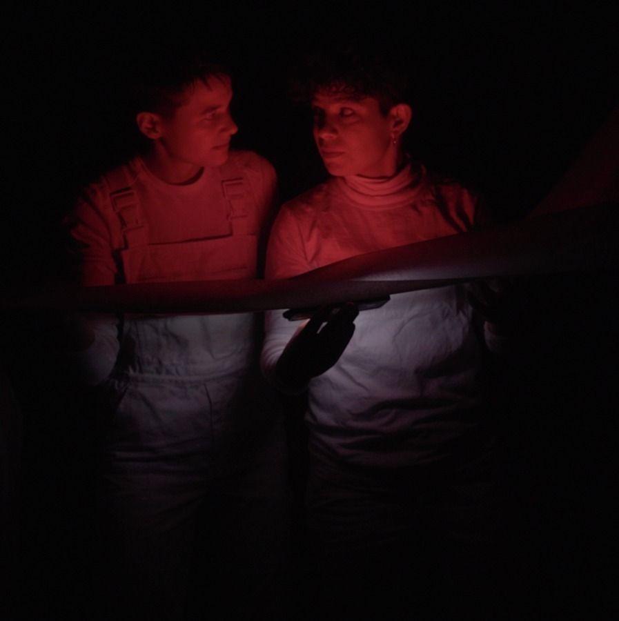 Zwei Menschen stehen im Dunkeln und schauen sich an. Ihre Gesichter und Oberkörper sind rot angeleuchtet.