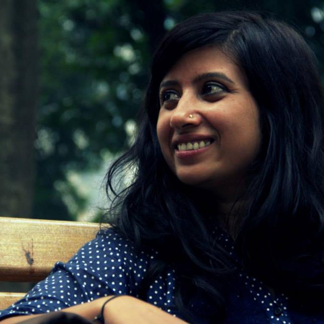 Neha Singh sitzt auf einer Bank und hat ihren Blick nach links oben gerichtet. Im Hintergrund sind grüne Baumkronen zu sehen.