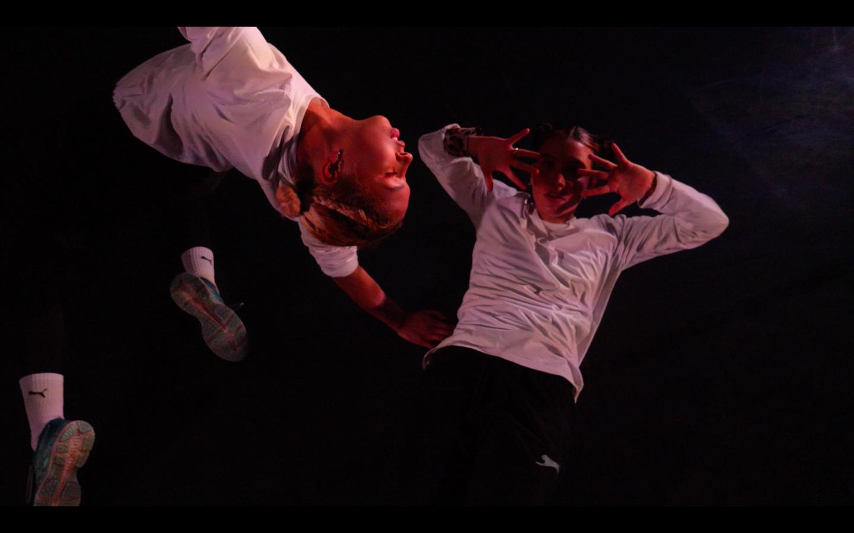 Beide Performerinnen sind zu sehen. Die eine springt mit gebeugtem Rücken hoch. Die andere hält ihre Hände vors Gesicht und blickt in die Kamera. Beide tragen schwarze Hosen und weiße Sweat-Shorts.